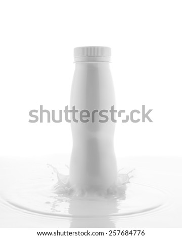 Clean blank white plastic bottle with milk splash on pure white background. - stock photo