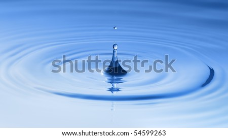 Clean blue drop of water splashing in clear water. Abstract blue background - stock photo