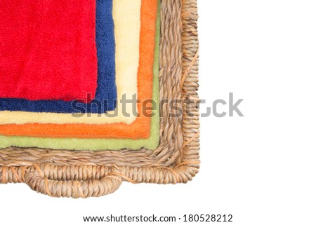 Clean colorful washed towels in a wicker basket neatly folded and stacked viewed from above giving a multicolored pattern of diminishing sizes to the red one on top, isolated on white with copy space - stock photo