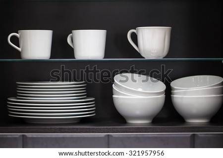 Clean Dishes and Other Tableware placed on a wooden shelf - stock photo