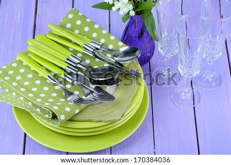 Clean dishes on wooden table on color background - stock photo