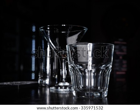 clean empty cocktail martini and old fashion rocks tumbler whiskey glasses on a dark bar counter with a black background