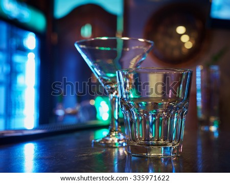 clean empty cocktail martini and old fashion rocks tumbler whiskey glasses on a dark bar counter with a black background  - stock photo