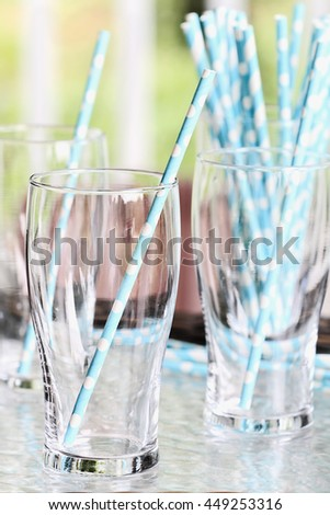 Clean empty drinking glasses with party straws on an outdoor table. Extreme shallow depth of field with selective focus on foreground. - stock photo