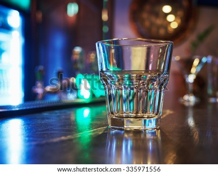 clean empty old fashion rocks tumbler whiskey glass on a dark bar counter with a background of neon lights and bokeh