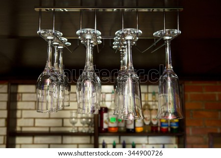 clean empty wine glasses and champagne hanging under the bar