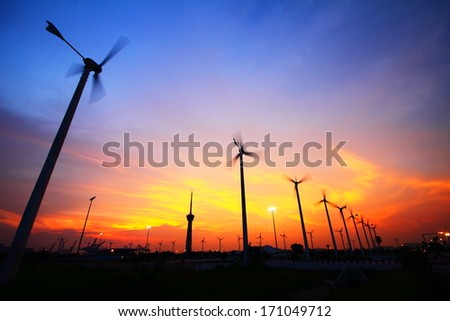 Clean energy wind turbine silhouettes are working at sunset