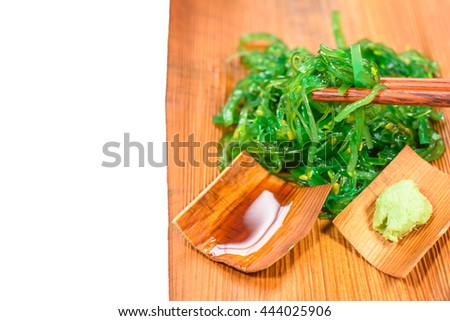 Clean food and good taste with fresh seaweed salad ,japanese food put on beautiful plate isolated on white background in the japan restaurant with copy space,Focus on seaweed salad on chopsticks - stock photo