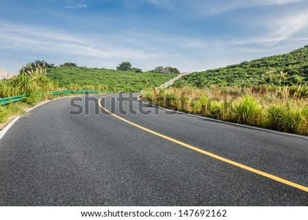 clean freeway go through the county field by day. - stock photo