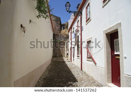 Clean little alley in Lisbon, Portugal with white house and wall - stock photo