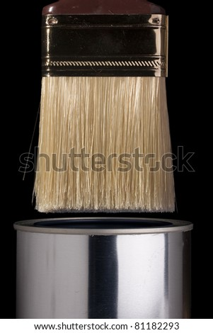 Clean paintbrush dipping into a silver can. - stock photo