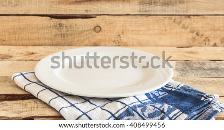 Clean plate with napkin on wooden background. - stock photo