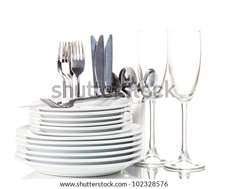 Clean plates, glasses and cutlery isolated on white - stock photo