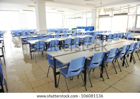 Clean school cafeteria with many empty seats and tables. - stock photo