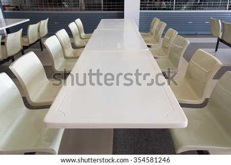 Clean school cafeteria with many empty seats and tables