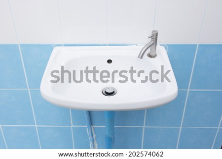 Clean sink and faucet at home toilet or bathroom - stock photo