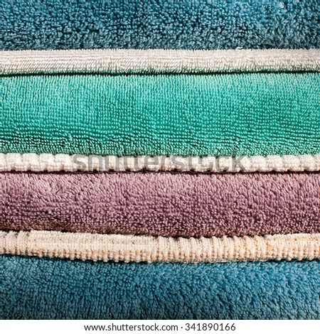 Clean stack of thick heavyweight bath towels and thin kitchen drying towels; close up square background - stock photo