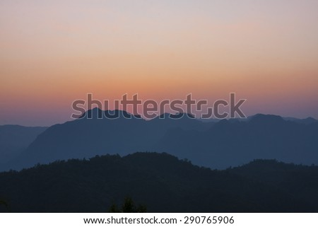 Clean sunset with silhouetted mountains.