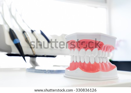 Clean teeth denture, dental jaw model in dentist's office. Dentistry instruments and equipment in the background - stock photo