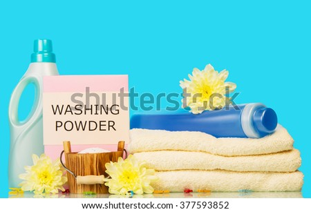 Clean towels with means for washing and yellow flowers on a blue background - stock photo