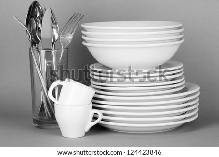 Clean white dishes on grey background - stock photo