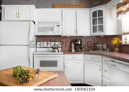 Clean white kitchen with asparagus on cutting board - stock photo
