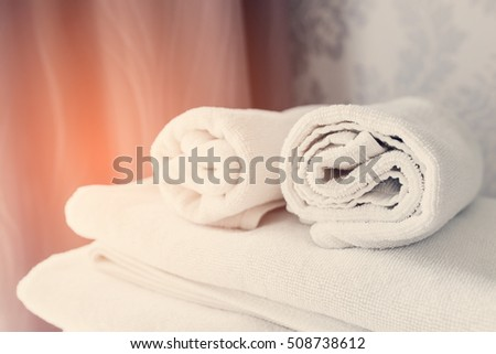 Clean white towels on the bed room.