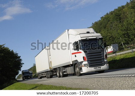 clean white truck driving on scenic highway with trees and forrest. trademarks removed. - stock photo