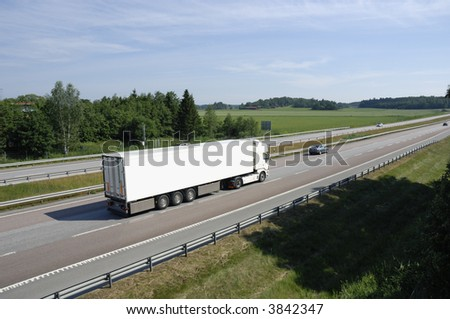 clean white truck driving past, elevated view from above - stock photo