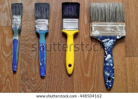 Clean yellow paintbrush with dirty blue brushes - stock photo