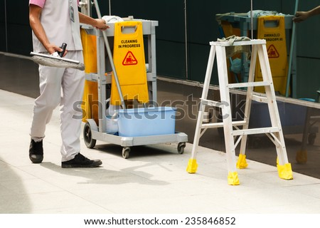 Cleaner in cleaning process with mop and stair - stock photo