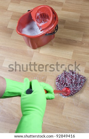 cleaner is mopping  wooden parquet floor - stock photo