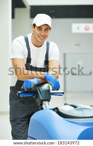 Cleaner male man workers with mop in uniform cleaning corridor pass or hall floor of business building - stock photo