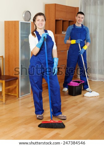 cleaners in uniform cleaning in room - stock photo