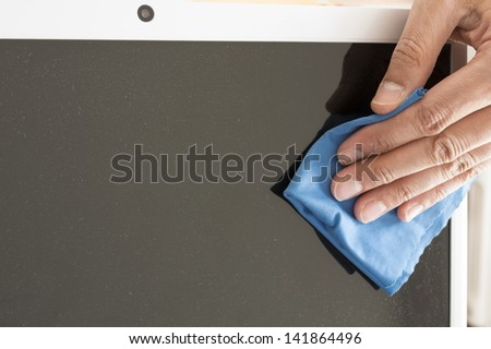 Cleaning a Flat screen with an antistatic cloth blue - stock photo