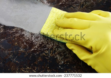Cleaning a greasy pan with yellow latex gloves                                - stock photo