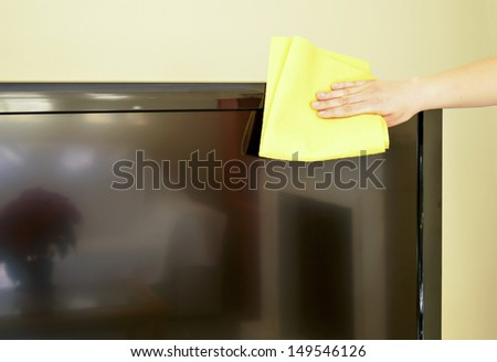 Cleaning a lcd TV with an antistatic cloth. - stock photo