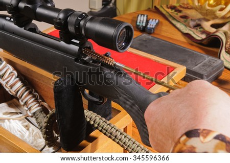 Cleaning a modern bolt action rifle, inserting the cleaning rod with a bore brush which has cleaning fluid on it into the chamber - stock photo