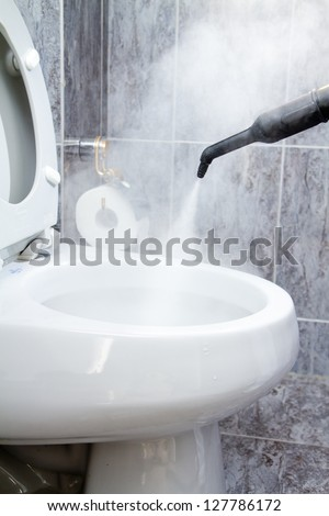 cleaning a toilet with steam - stock photo