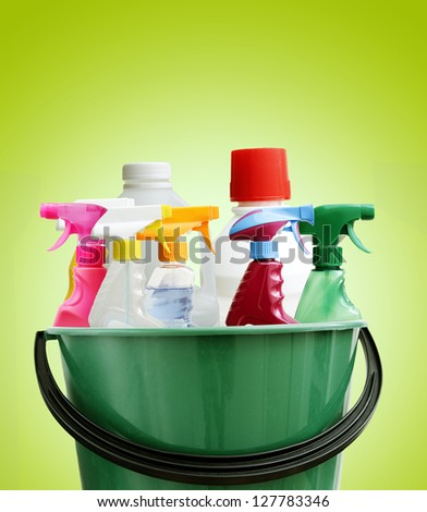 Cleaning bottles in bucket. Green background - stock photo