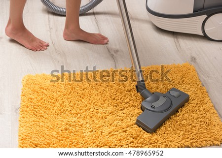 Cleaning bright orange carpet. Housewife cleans the carpet in the living room. Powerful vacuum cleaner for domestic cleaning.