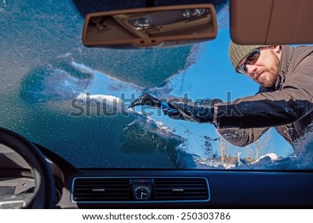 Cleaning Car From Snow. Men Cleaning Car Windshield From Snow and Ice After Snow Storm. Photo Taken From Inside the Vehicle. - stock photo