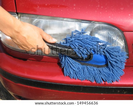 Cleaning car front light with soft brush, close up