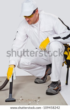 Cleaning cement floor with vacuum cleaner - stock photo