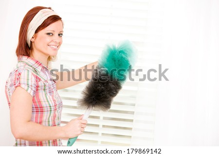 Cleaning: Cheerful Woman Dusts Window Blinds - stock photo