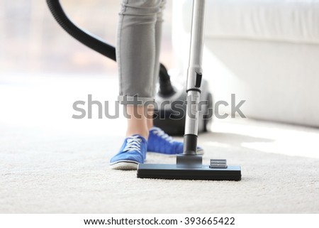Cleaning concept. Young woman cleaning carpet with vacuum cleaner, close up - stock photo