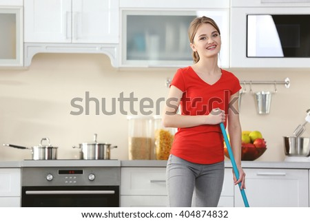 Cleaning concept. Young woman washing floor on the kitchen