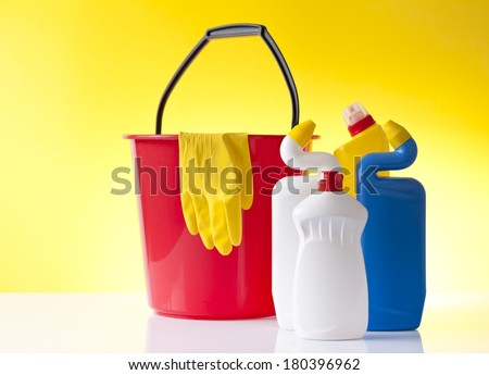 cleaning detergents and red bucket with gloves