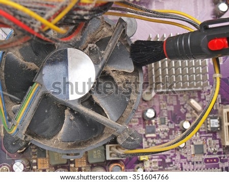 Cleaning dirty desktop computer processor fan from dust by special brush close up. - stock photo