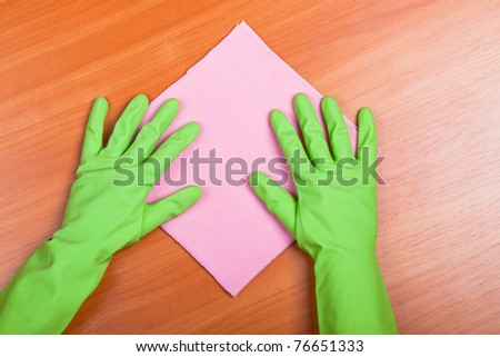 Cleaning furniture table in green gloves with pink sponge - stock photo